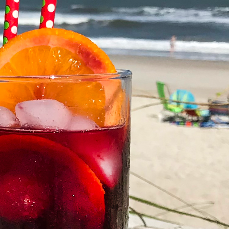 the orange in the glass of sangria with the ocean in the background