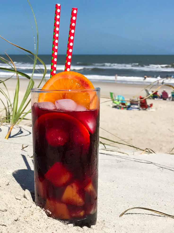 Bring the Beach Tropical Sangria Recipe glass in sand with ocean and beach chairs in background