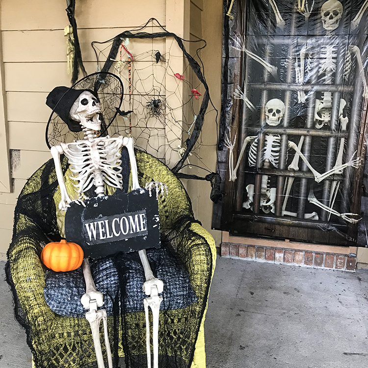 Eerie Entryway Decor for Halloween centerpiece - skeleton in chair laughing at skeletons inside front door