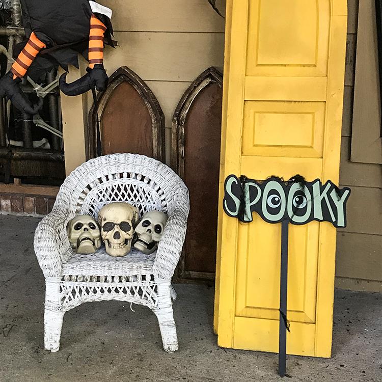 3 spooky skulls in small wicker chair