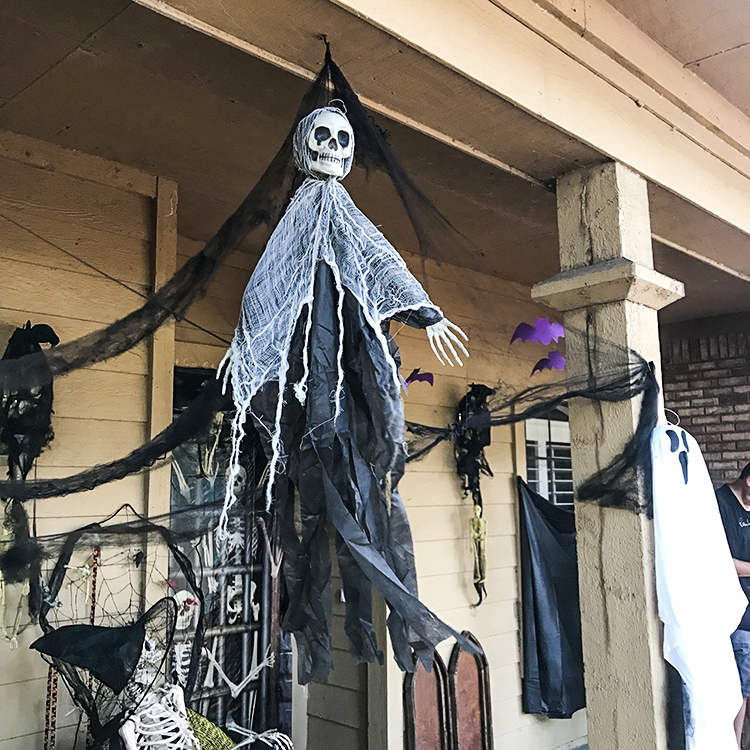 zombie skeleton hanging from soffit and other Eerie Entryway Decor for Halloween